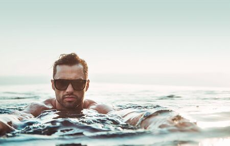 Portrait of a handsome, muscular guy relaxing in a warm tropical water 写真素材 - 124942693