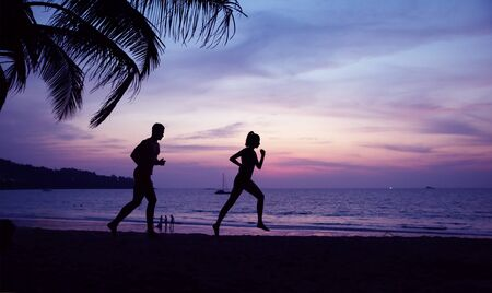 Young, fit couple doing jogging on the tropical beach Imagens