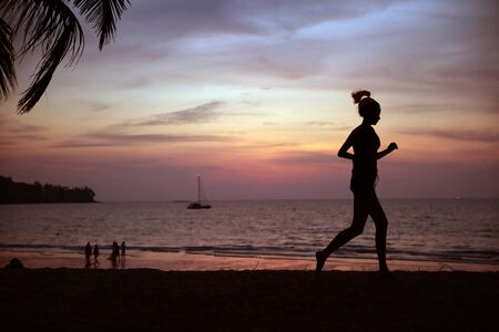 Young, fit woman doing jogging on a tropical beach