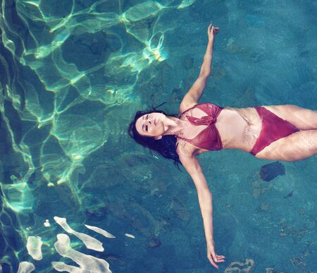 Sensual brunette woman relaxing in the tropical, luxurious pool Imagens