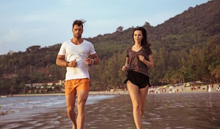 Attractive couple doing jogging on a beach
