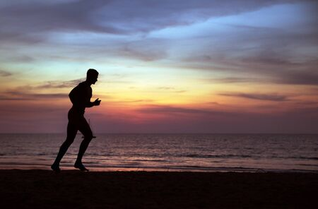 Young, fit guy doing jogging on a tropical beach