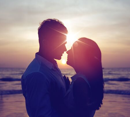 Romantic portrait of a young, attractive couple with fabulous sunset in background Imagens