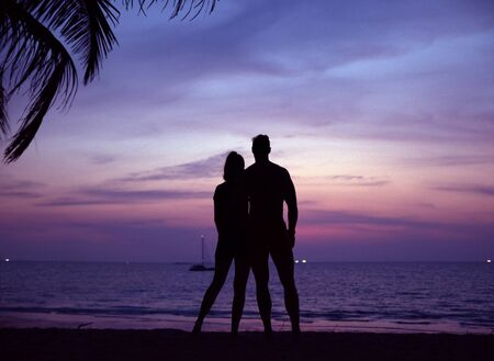 Relaxed, young couple watching a tropical sunset