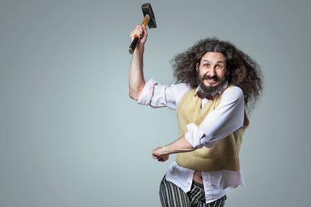 Portrait of an eccentric, aggresive nerd holding a hammer