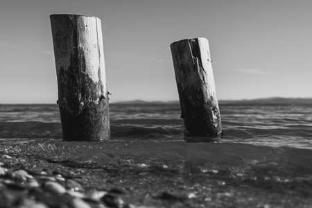 two wooden piles washed by the waters of the lake with the mountains in the background in monochrome
