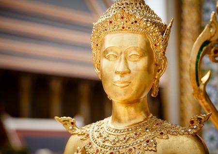 the grand palace: Golden Kinnari statue outside Buddhist temple at Grand Palace, Bangkok. Stock Photo