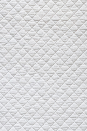 quilted: Closeup of white quilted fabric. Stock Photo