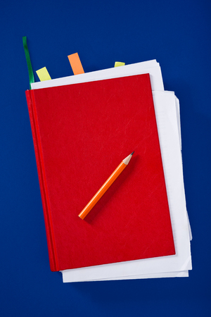 pencils  clutter: Red diary with pencil on blue background