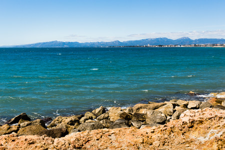 Stony shore with Salou city and mountains in background. Stock Photo
