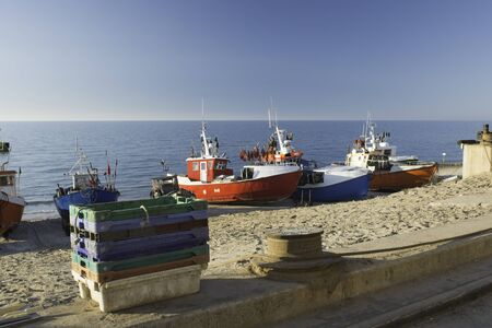 Fishing boats standing on the beach in the port and summer resort in Chlop