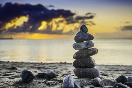 pile of stones on the beach at sunrise