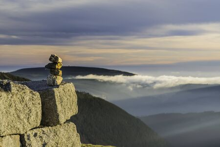 Pile of stones stacked in the mountains against the backdrop of a beautiful panorama with the setting sun against the background of the sky of fog and clouds