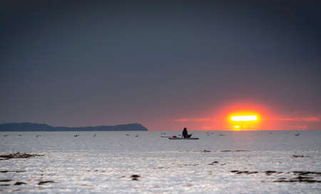 Silhouette of the girl on a surfboard at sunset
