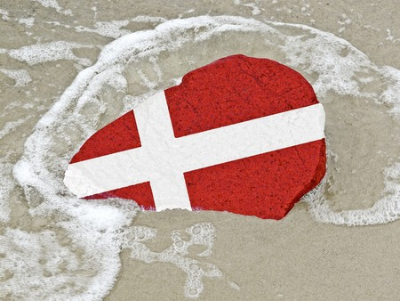 neighbouring: Flag of Denmark on a stone on the Baltic Sea beach