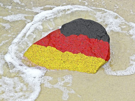 Flag of Germany on a stone on the Baltic Sea beach photo
