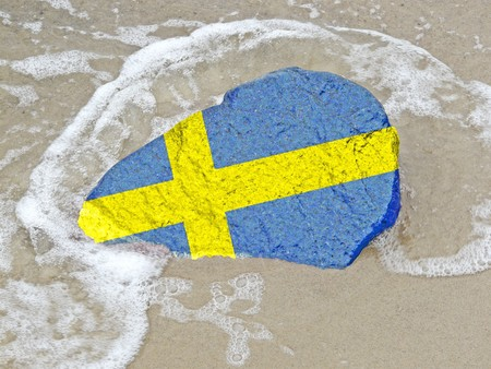 neighbouring: Flag of Sweden on a stone on the Baltic Sea beach Stock Photo