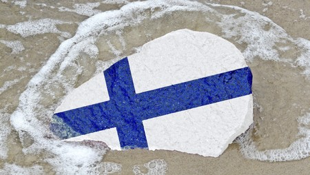 erratic: Flag of Finland on a stone on the Baltic Sea beach Stock Photo