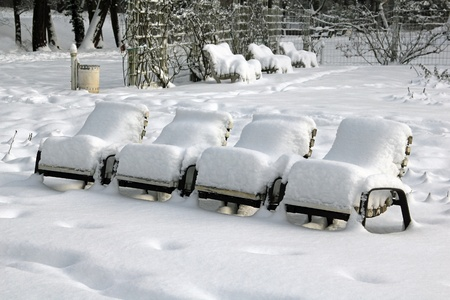 Row of snow-covered park-chairs in the municipal park Pankow in Berlin, the German capital photo