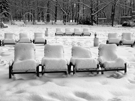 Rows of snow-covered park-chairs in the municipal park Pankow in Berlin, the German capital photo