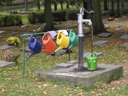 Colourful watering cans on a cemetery photo