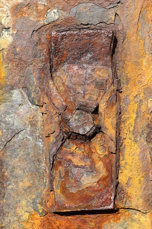Rusty fragments of a hexagonal bolt head with flange photo