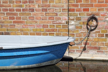 A blue rowing boat is docked at a brick wall photo