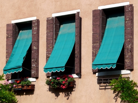 awnings: Three windows with blue-green awnings and flower boxes at a house in Venice