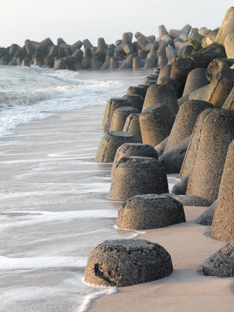 seawall: The coastline of the Island of Sylt is perpetually changed by erosion. Barriers from tetrapods made of concrete shall protect the beach.