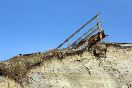 Remains of wooden stairs on a destroyed dune photo
