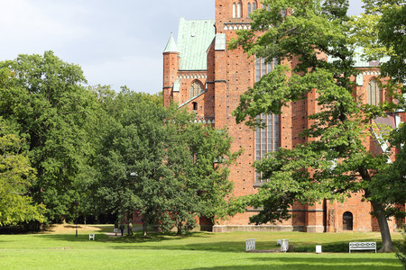 minster: English garden and the West facade of Doberan Minster in North Germany