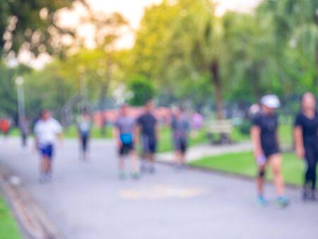 Des gens flous marchent, courent dans le parc
