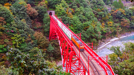 Train on Shin Yamabiko red bridge cross the river at Unazuki station in Kurobe gorge