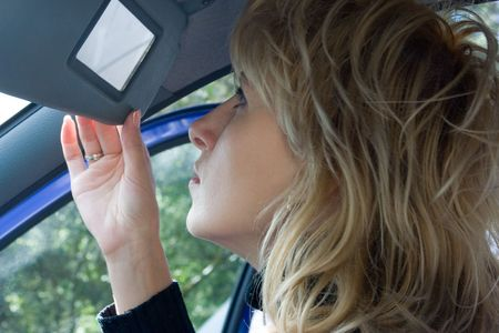 primp: donna del blonde che osserva in piccolo specchio auto