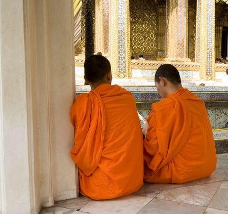 dos monjes budistas sesi�n en traditoinal t�nicas de color naranja Foto de archivo - 2249555