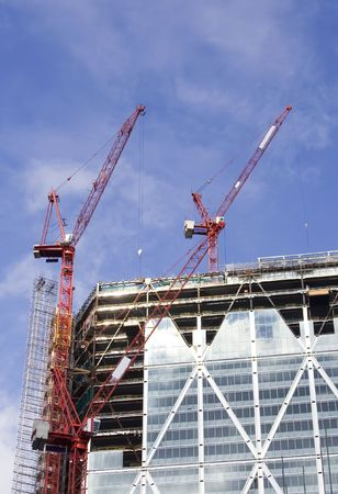 erect: Large cranes over a building in construction Stock Photo