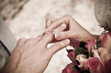 bride wear ring on groom's finger Stock Photo