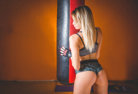 Beautiful young adult girl posing happy with boxing bag in modern fitness center.