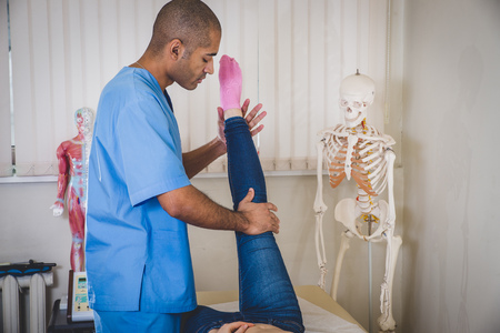 Professional male doctor advises and conducts examination of back of cute girl who has come to reception and feels discomfort in back. Guy physician with European-style with short haircut dressed in