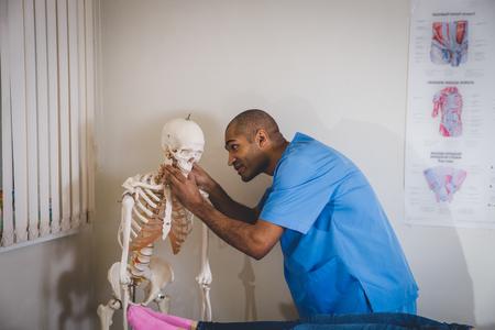 Male student stood behind human skeleton 스톡 콘텐츠
