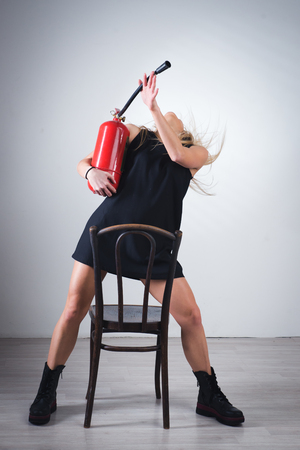 Attractive tall woman in red dress with fire extinguisher in hand