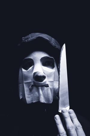 Maniac or criminal in mask holding knife Zdjęcie Seryjne