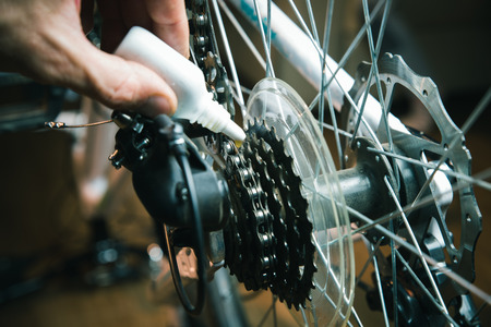 Closeup of male hands cleaning and oiling a bicycle chain and gear with oil spray.
