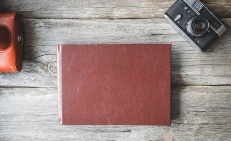 Old photo album lying on a wooden surface. Retro album.