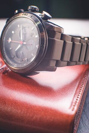 Vintage watch on a brown leather wallet. Classic Wristwatch. (Vintage Style Color Process)