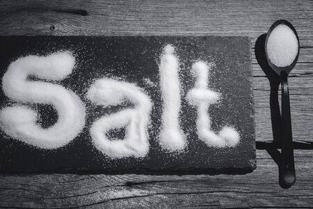 Salt written on counter in spilled salts from shaker Stok Fotoğraf