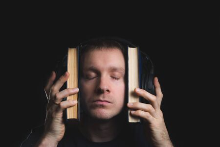 Attractive young man sitting listening to music on a set of stereo headphones in his study at home in front of a bookcase filled with books