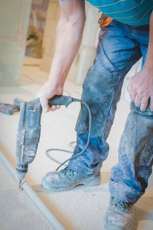 A worker using a drill to break cement floor surface Stok Fotoğraf