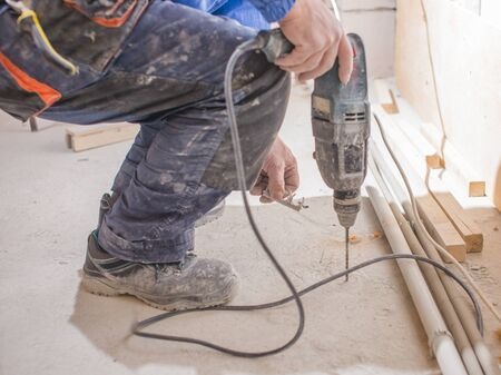 Electrician installing heating red electrical cable wire on cement floor in unfinished room. Renovation and construction, comfortable warm home concept. Stok Fotoğraf