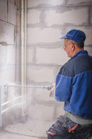 builder with hammer breaking wall indoors Stok Fotoğraf